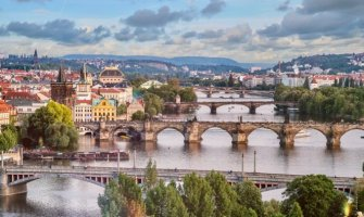 areal image of Prague looking over the river with 4 bridges crossing the river there are colorful buildings to the left and trees to the right