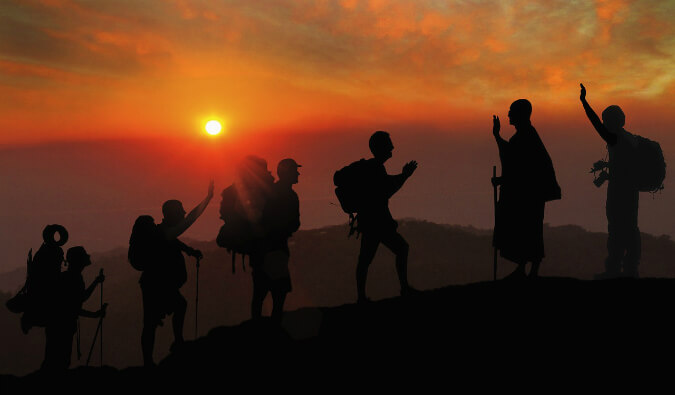 4 hikers with backpacks walking up a mountain being greeted by 2 people at the top all in silhouette at red sunset