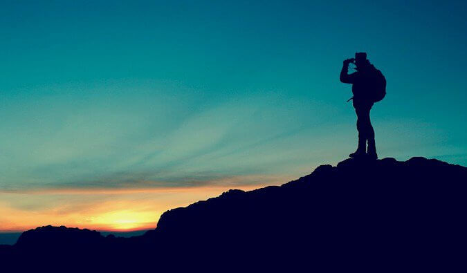 A man on a mountain as the sun goes down