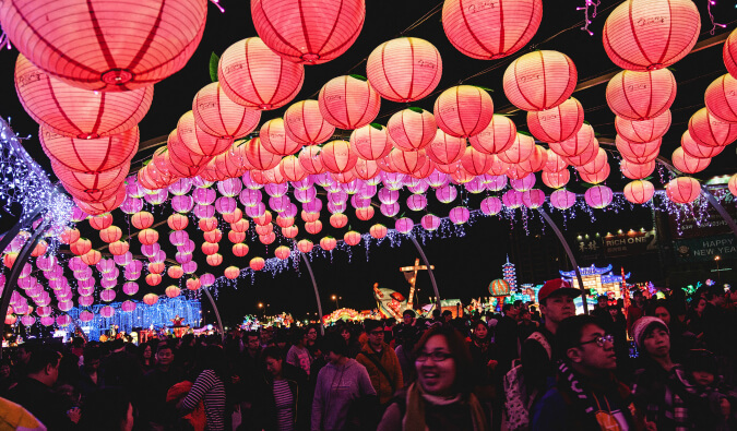 people celebrating under the pink and red lanterns at the lantern festival in Taiwan