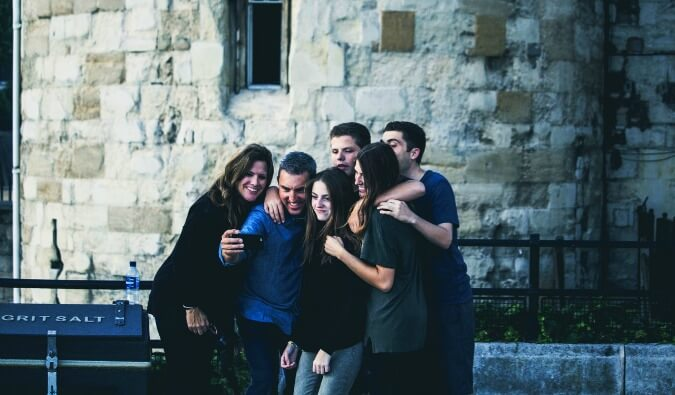 group of 6 friends huddled close together taking a selfy