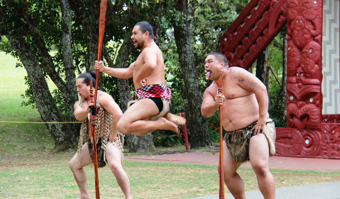 three Maori men in traditional dress performing a ritual dance