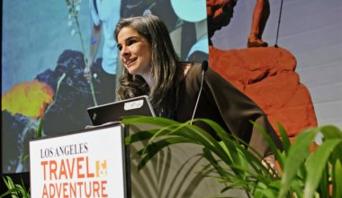 Image of Pauline Frommer talking into a microphone at Travel Adventure conference