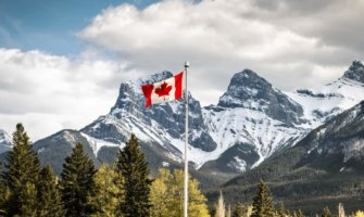 A Canadian flag waving in the mountains