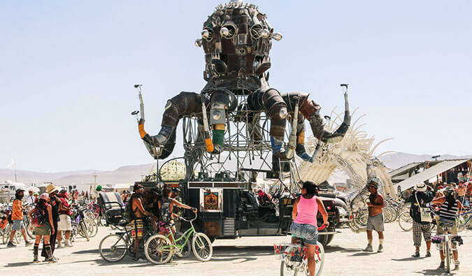 people on bikes around a giant sculpture at Burning Man Festival