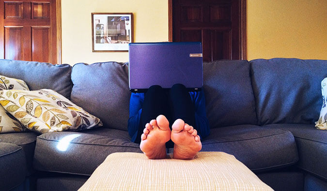 Man on a couch with feet up towards the camera face obstructed by laptop