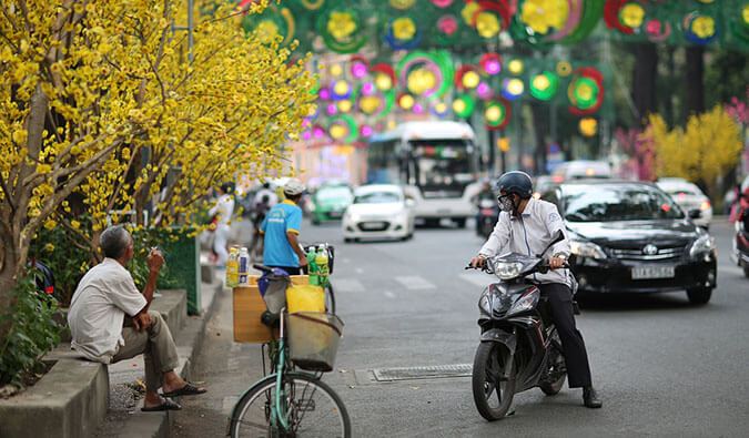 busy street scene in Vietnam. Man on a moto looking behind him at the traffic