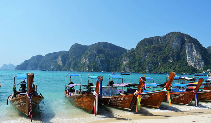 classic shot of Thai wooden long boats tied up on a Thai beach