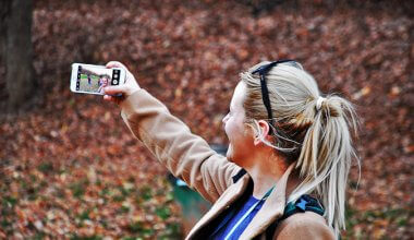 woman in the woods taking a selfy with her smart phone