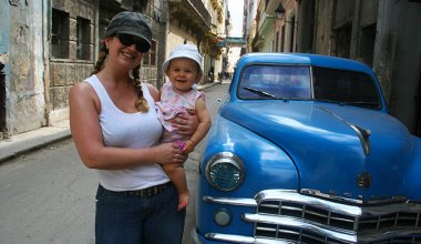 woman holding a baby in Cuba next to a blue classic car