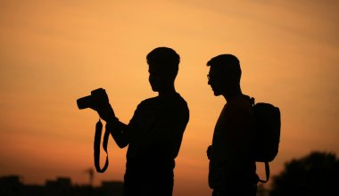 two men looking at photos on a DSLR camera silhouetted at sunset