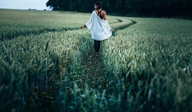 A woman alone walking in tall grass