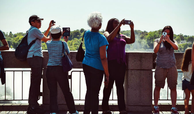 5 people on a bridge taking pictures with phones and cameras