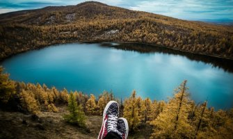 feet wearing sneakers front centre above a beautiful lake surrounded by trees and greenery in the background