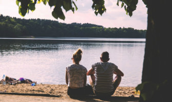 A couple sitting by the lake together