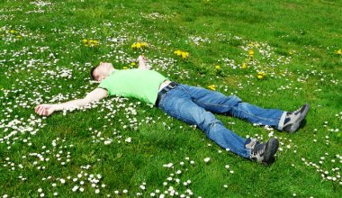 man laying on his back on grass covered in daisies