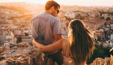 man and woman looking down over a city during the golden hour before sunset