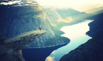 woman doing tree yoga pose on a cliff edge over a lake