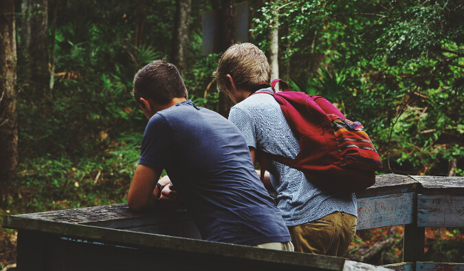 to men stood next to each other on a wooden bridge looking out into a forest