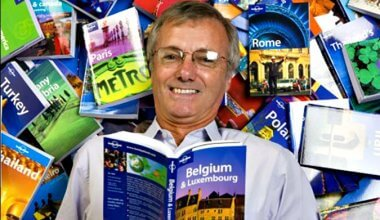 Tony Wheeler from Lonely Planet surrounded by Lonely Planet books and reading a guide to Belgium