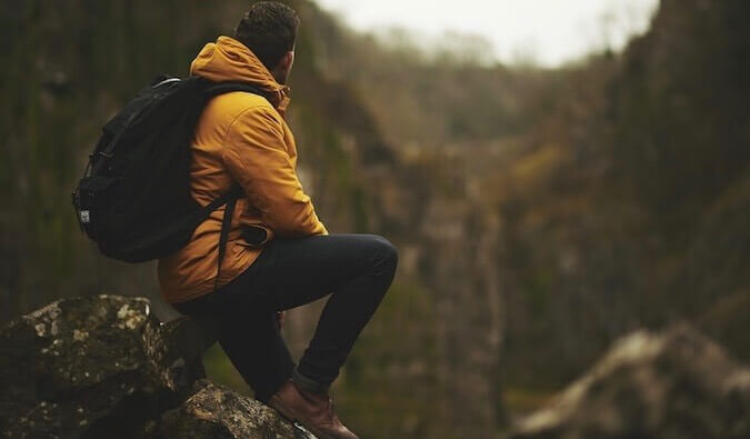 A man in a yellow coat looking out over the mountains
