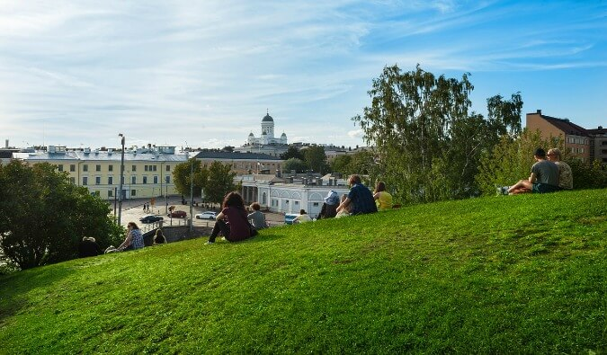 people sat on the grass looking down over the city of Helsinki