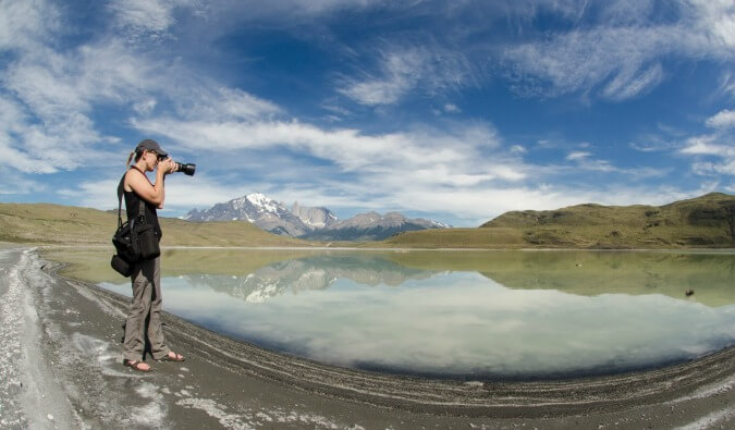 woman taking a photo with her DSLR camera of a mountain reflected in a lake