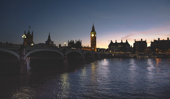 view over the river Thames at night looking towards big ben and The Houses of Parliament