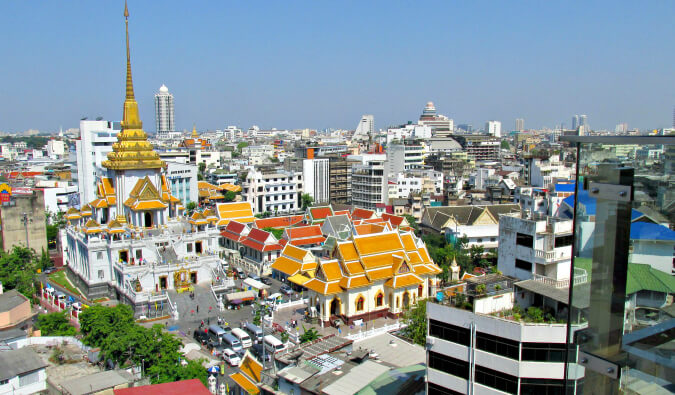 areal image of Bangkok with a temple to the left with a gold roof