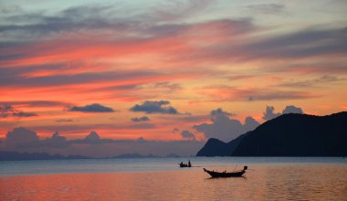 sunset in Thailand looking out across the sea with two fishing boats in the water