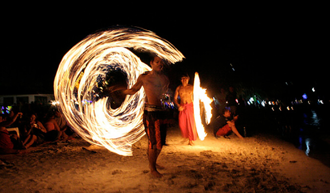 2 men dancing with fireballs on a beach at a full moon party