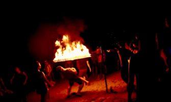 Tourists playing limbo under a fire stick
