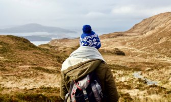 Woman stood in the hills in Ireland wearing warm winter clothing and a bobble hat.