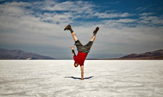 Man in wide open space with snow on the ground stood upside down on one hand