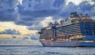 A large cruise ship sailing into the cloudy sunset