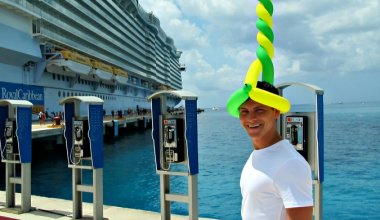 Nomadic Matt pictured with a balloon hat on at a port with a Royal Caribbean cruise ship in the background to the left