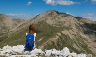 woman with hiking stick and backpack sat facing away from camera looking out to the mountains