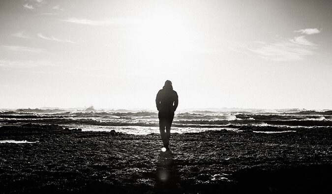 man walking along the beach alone in black and white