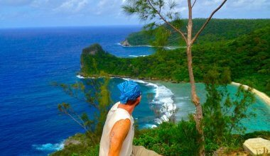 man sat front and centre looking down and out over the sea to the left and greenery to the right