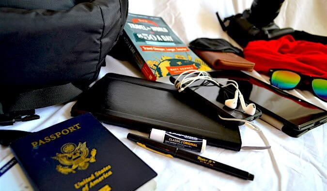 Passport, travel guide, headphones, pen, chapstick and other items laid out ready to pack for travel.