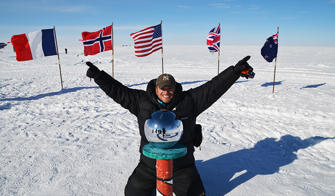 Man celebrating an achievement with arms in the air in a place covered in snow with various countries flags behind him