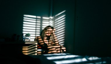 woman looking sad in the corner of a room with shadows over her