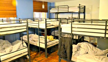 hostel dorm room with 4 sets of bunk beds in a small space