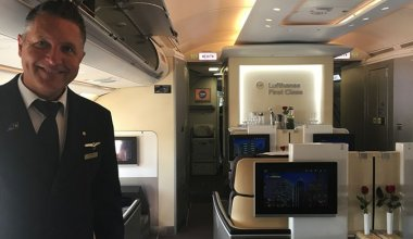 cabin crew in the business class section of an airplane