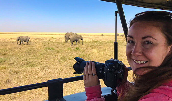 Helen holding a DSLR camera ready to take a photograph of some elephants in the wild