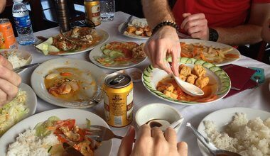plates of Chinese food and beer cans on a table with peoples hands in the shot preparing to eat