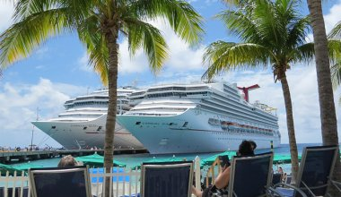 Two cruise ships docked in the Caribbean. People in the foreground sunbathing on sun beds reading