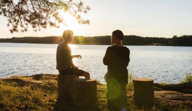 Two travelers having a conversation by a lake
