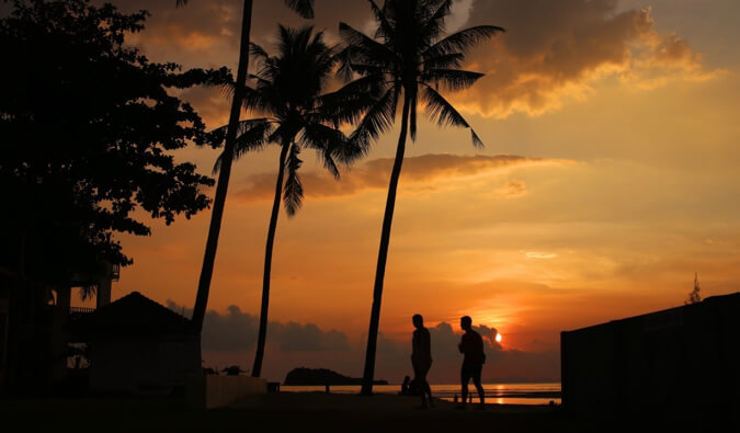 sunset silhouette image of two people walking on a beach in Koh Lanta Thailand