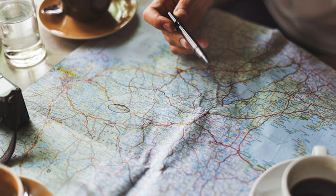 a mans hand holding a pen pointing towards a place on a map, camera, coffee cups, and a glass of water